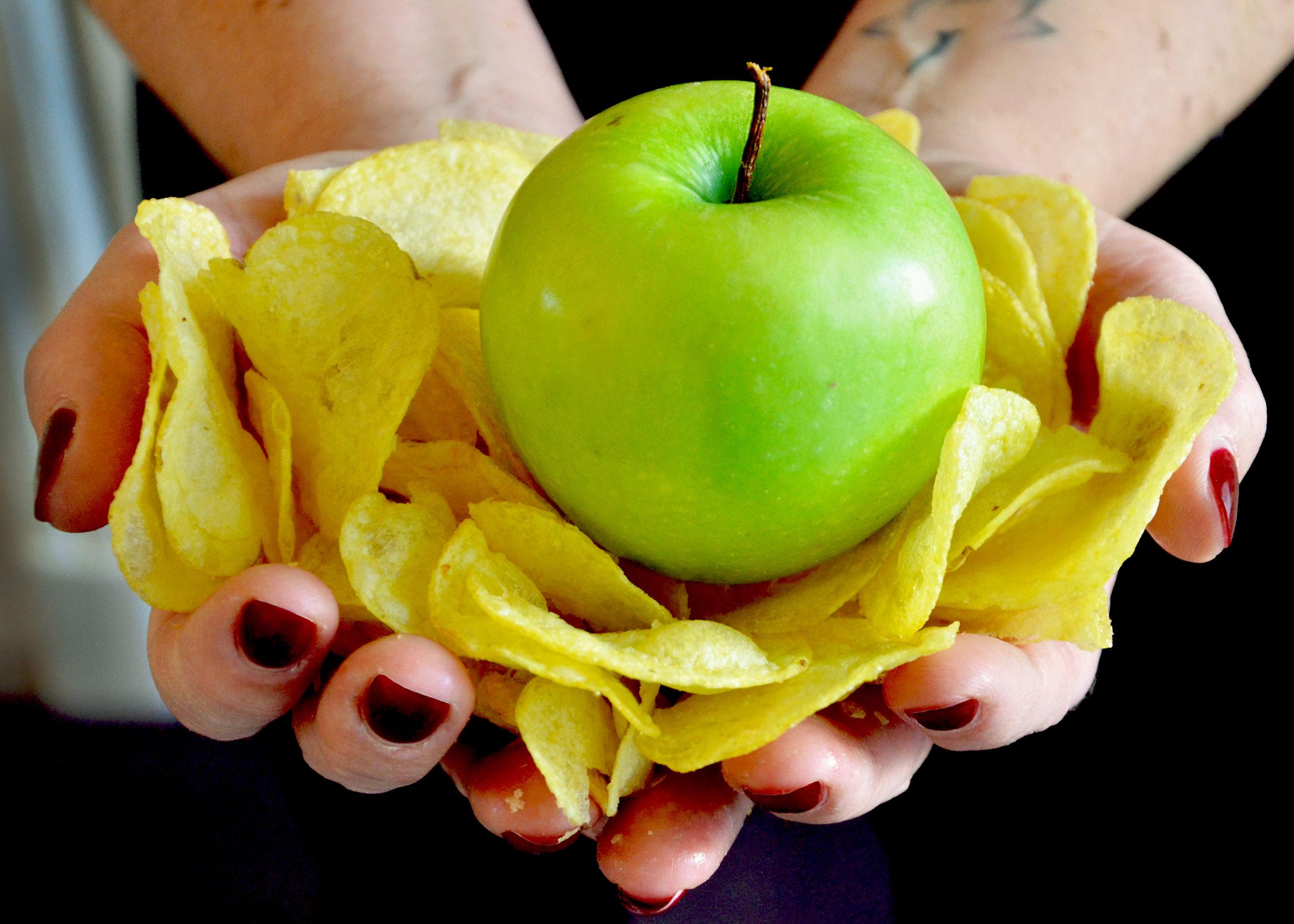 chips en een groene appel. Gezond versus ongezond. Afscheid nemen van ongezonde gewoonten