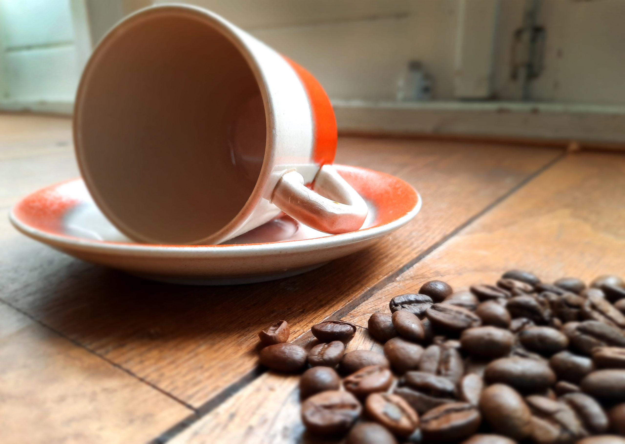 koffie kopje liggend op schoteltje met koffiebonen erbij. Ondersteunden aan gedicht Nog-even-niet. Troost koffie