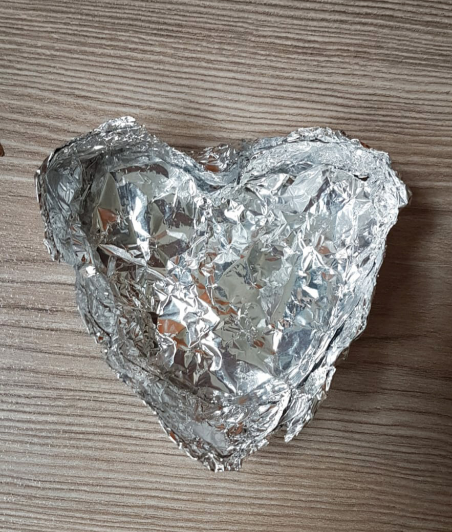 duizend stukjes liefde. Zilveren aluminium hart. Gevouwen van aluminiumfolie als bakje. Liefde blijft bestaan
